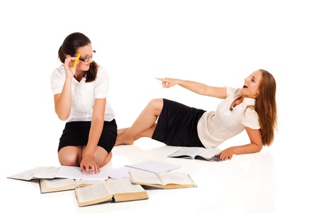 Two students are preparing for the exams. One has books, other - beauty magazine. Who will get a better mark?NOTE: Isolation with shadows! Stock Photo - 10930455