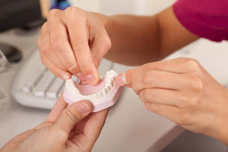 Dentist is showing patient how to use dental floss.