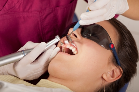 Dentist is cleaning patients teeth with special whitening paste