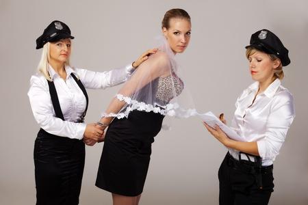 under arrest: Hen party mates are taking fiancée under arrest. Stock Photo