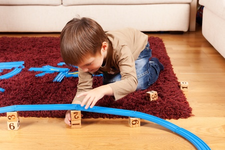 Little boy is building toy railroad using bricks photo