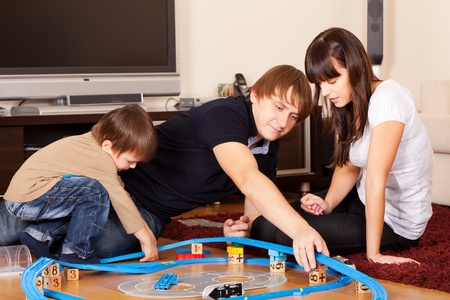 Family is playing toy railroad and bricks