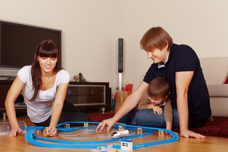 Family is playing toy railroad and bricks Stock Photo - 11801236