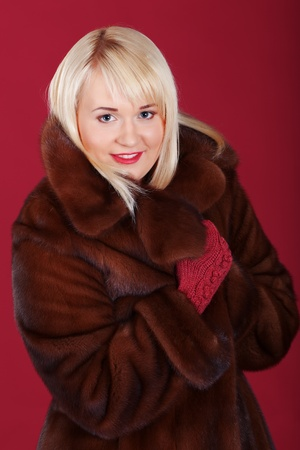 Girl in winter coat on pink background photo