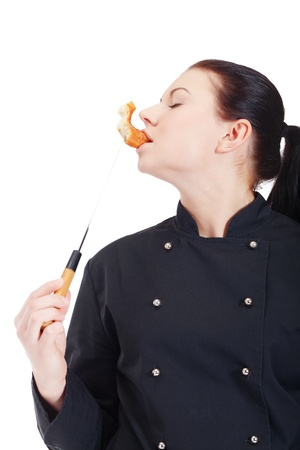 Chef is eating doughnut while cooking photo
