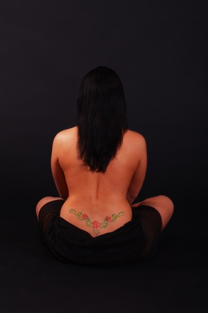 Young woman with a colored tattoo sitting on the black Stock Photo - 11929099