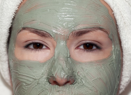 Young woman in green mud mask and wrapped in a tower photo