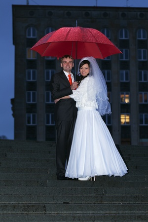 Just married couple with umbrella under the rain photo