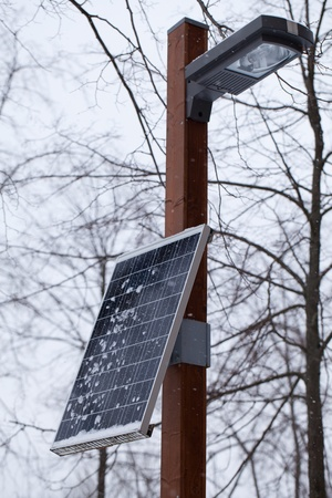 One small solar battery, which provides electricity not only for lamp, but for sockets on post Stock Photo
