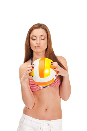 Young girl in swimwear is holding deflated ball for volleyball and thinking of coming summer photo