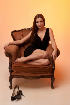 evening gown: Woman sitting on a chair in the evening gown and in brown tones Stock Photo