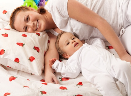 Mother and son are lying on the bed and looking at camera  Focus is on baby Stock Photo - 12874630