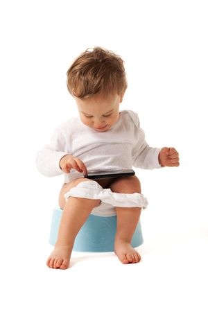 Boy sitting on a chamber pot playing with smartphone