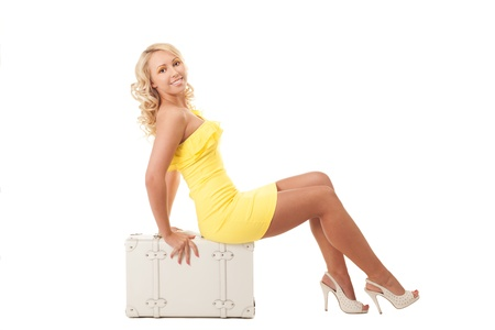 Young blond girl in yellow dress is sitting on a suitcase almost ready for vacations Stock Photo