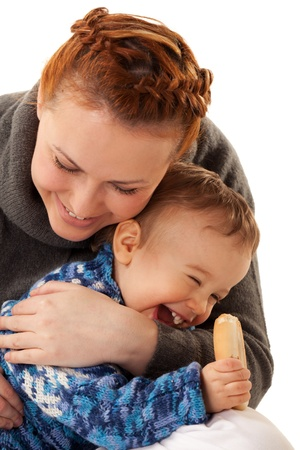 nibbling: Laughing boy is nibbling dry biscuit sitting on mothers knees