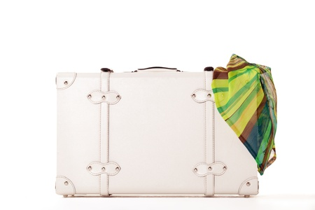 White suitcase on white background, standing on white surface with dress sticked out