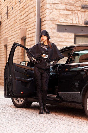 Elegant women posing near the luxury car photo