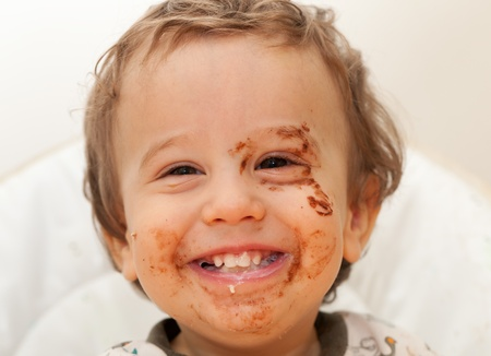 Laughing baby dirty with chocolate food Stock Photo - 13389786