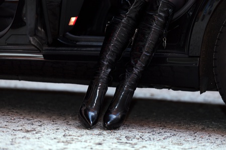 Unrecognizable girl in boots is getting out of the car photo