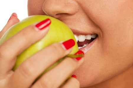 Close-up of a person biting apple photo