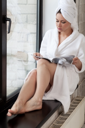 Woman in white bathrobe reading magazine sitting on windowsill Stock Photo