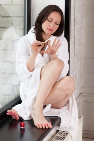 Girl in bathrobe making manicure and pedicure photo