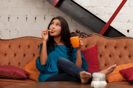 Girl on sofa with tea and biscuit photo