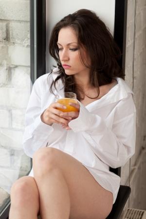 Girl sitting on windowsill with glass of juice photo