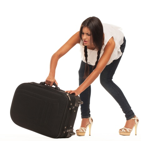 Girl is trying to lift her luggage up  isolated, standing on white surface