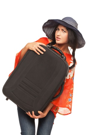 Girl is trying to lift her luggage up