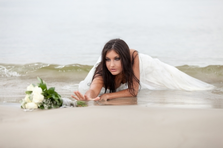 Abandoned bride is trying to reach bridal bouquet photo
