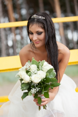 Happy bride with bouquet smiling in the rain Stock Photo