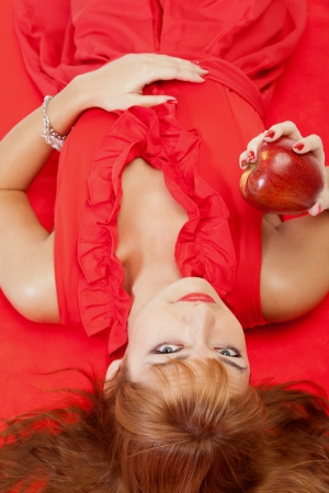 Red-haired girl in red dress with red apple lying on red carpet photo