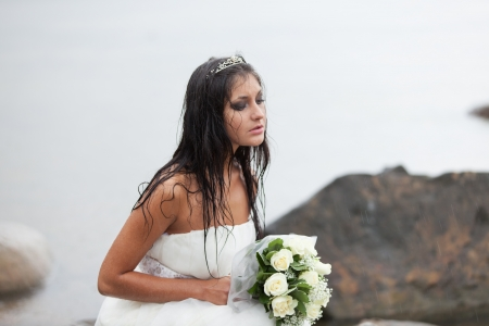 Sad bride sitting on the sea-shore and crying in the rain photo