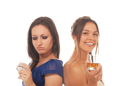 One girl is disappointed because of empty glass while other is happy to have it filled
