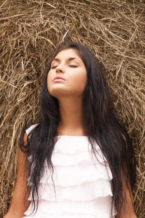 Charming girl sleeping on a hayloft photo