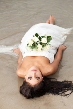 Tired bride on a beach Stock Photo - 14847290