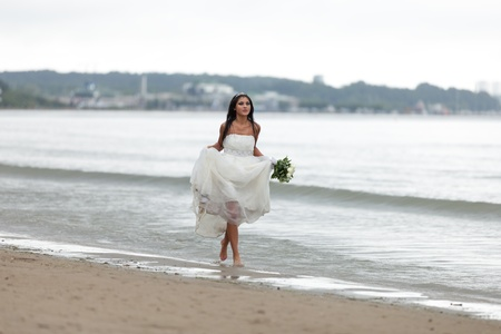 Runaway bride on a beach photo