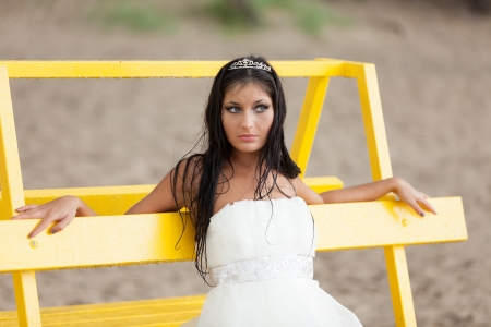 Runaway bride sitting on bench photo