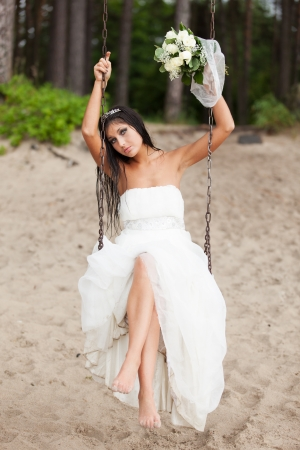 Runaway bride sitting on a swing