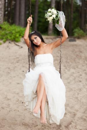 Runaway bride sitting on a swing