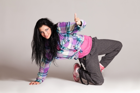 Girl performing hip-hop dance on gray photo