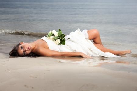 Runaway bride laying in the sea Stock Photo