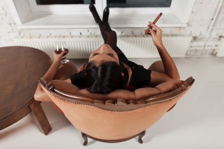 savour: Girl relaxing at home with glass of brandy and cigar Stock Photo