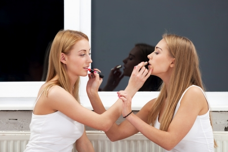 Two girls applying make up to each other photo