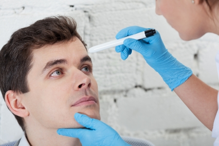 Doctor checking tired eyes of patient Stock Photo