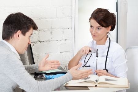 Doctor joshing patient with reflex hammer and nail Stock Photo - 16887173