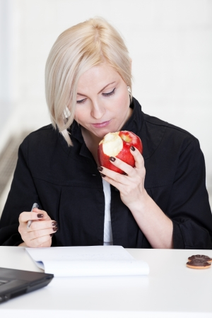 Business woman having short lunch during work photo