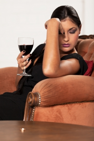 Girl with red wine is taking hard decision Stock Photo