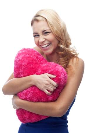 Laughing girl with heart shaped pillow on isolated white photo